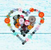 Sewing buttons heart on wooden background — Foto Stock