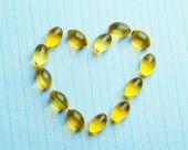 Heart of cod liver oil, on blue background — Stock Photo