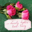 Beautiful rosy twig with tag on wooden background — Stock Photo #71949443