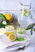 Fresh water with lemon and cucumber in glassware on wooden background — Stock Photo