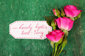 Beautiful rosy twig with tag on wooden background — Стоковое фото