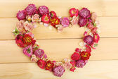 Heart of beautiful dry flowers on wooden background — Stock Photo