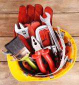 Construction tools in helmet on wooden background — Stock Photo