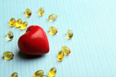Red heart and cod liver oil, on blue background — Stock Photo