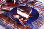 Delicious chocolate cake with icing in plate on table, closeup — Stock Photo