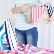 Electric iron and shirt on ironing board in room — Stock Photo #72145073