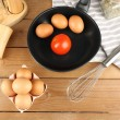 Still life with eggs and pan on wooden background — Stock Photo #72145499