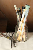 Paintbrushes in vase on wooden background — Stock Photo
