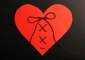 Stitched heart on black background — Stock Photo
