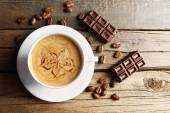 Cup of coffee latte art with grains and chocolate on wooden table, top view — Stock Photo