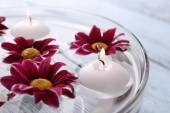 Bowl of spa water with flowers and candles on wooden table, closeup — Stock Photo