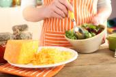 Woman cooking salad with grating cheese, close-up — Stock Photo