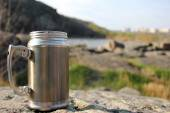 Thermos travel cup on nature background — Stock Photo