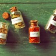Assortment of spices in glass bottles on wooden background — Stock Photo #72162439