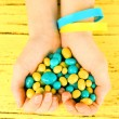 Hands with blue-yellow candies - colors of flag of Ukraine, on wooden background — Stock Photo #72184941