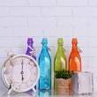 Interior design with alarm clock, plant and decorative colorful glass bottles on tabletop on white brick wall background — Stock Photo #72187641