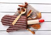 Set of kitchen utensils with cinnamon sticks and star anise in mitten on wooden background — Stock Photo