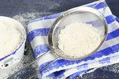 Sifting flour through sieve on wooden table, closeup — Stock Photo