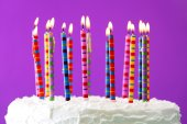 Birthday cake with candles on color background — Stock Photo