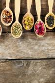 Collection of tea and natural additives in wooden spoons, on old wooden table — Stock Photo