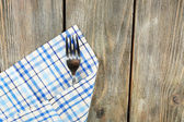 Checkered napkin with fork on wooden table background — Stock Photo