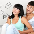 Dreaming concept. Beautiful loving couple sitting on sofa in room on grey background — Stock Photo #72477589