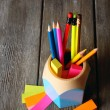 Colorful pencils in holder with sticky notes on wooden planks background — Stock Photo #72477919