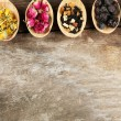 Collection of tea and natural additives in wooden spoons, on old wooden table — Stock Photo #72478945