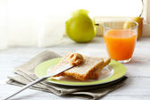Toasts with peanut butter on plate with cup of tea and juice on light background — Stock Photo