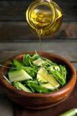 Poring green salad with olive oil on wooden table, closeup — Stock Photo