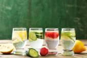 Glasses of different home made freshness healthy vitamin-fortified water on wooden table — Стоковое фото