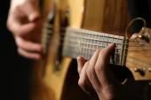 Jovem tocando violão em fundo escuro — Fotografia Stock