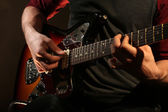 Young man playing on electric guitar close up — Stock Photo