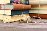 Stacks of books with dry flowers and twine on table close up — Stock Photo