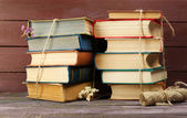 Stacks of books with dry flowers and twine on wooden background — Stock Photo