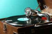 Gramophone with vinyl record on table on green background — Stock Photo