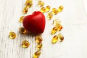 Red heart and cod liver oil, on wooden background — Stock Photo