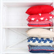 Decorative pillows on shelf — Stock Photo #72711343
