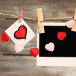 Bright hearts and photo paper hanging on rope on wooden background — Stock Photo #72714571