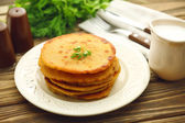 Stack of corn tortillas with stuffing and greens on wooden table background — Stock Photo