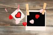 Bright hearts and photo paper hanging on rope on wooden background — Foto de Stock