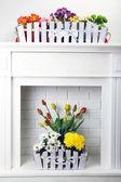 Beautiful flowers in ornamental flowerpot on mantelpiece — Stock fotografie
