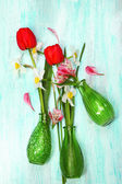 Beautiful flowers in vases on wooden background — Stock Photo