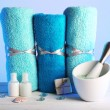 Rolled towels with sea salt, small plastic bottles of shampoo, bar of soap and crystals on wooden table and light colorful background — Stock Photo #72750871