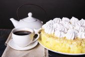 Tasty homemade meringue cake and cup of tea on wooden table, on grey background — Stock Photo
