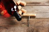 Glass bottle of wine with corks and corkscrew on wooden table background — Stock Photo