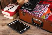 Packing suitcase for trip on wooden background — ストック写真