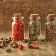 Assortment of spices in glass bottles on wooden background — Stockfoto #72766939