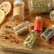 Assortment of spices in glass bottles on cutting board, on wooden background — Stock Photo #72768085