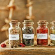 Assortment of spices in glass bottles on cutting board, on wooden background — Stock Photo #72768105